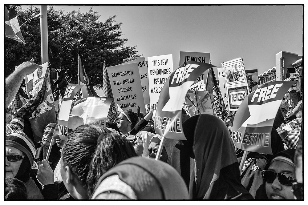 """A black and white photo of a protest with signs that say """"Free Gaza"""""""