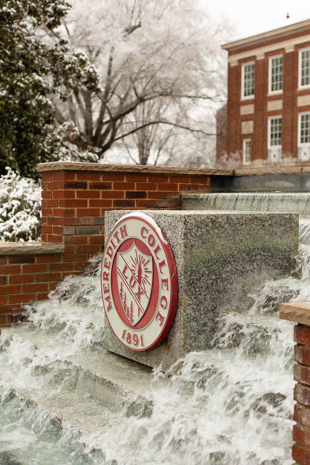 """The front fountain at Meredith College with the """"lux"""" symbol"""