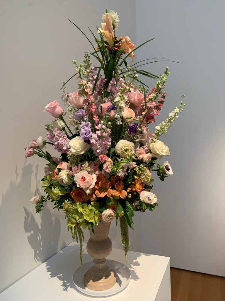 A beige vase with mainly pink flowers and greenery