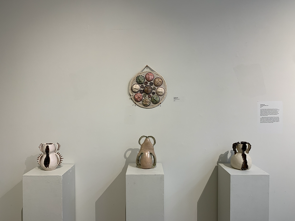 Three small , earth-toned ceramic pots on pedestals with another circular ceramic piece hanging above them