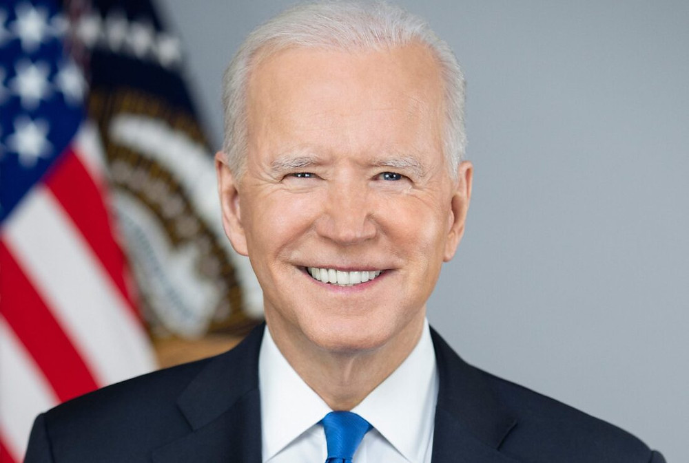 Joe Biden smiling at the camera in front of an American flag