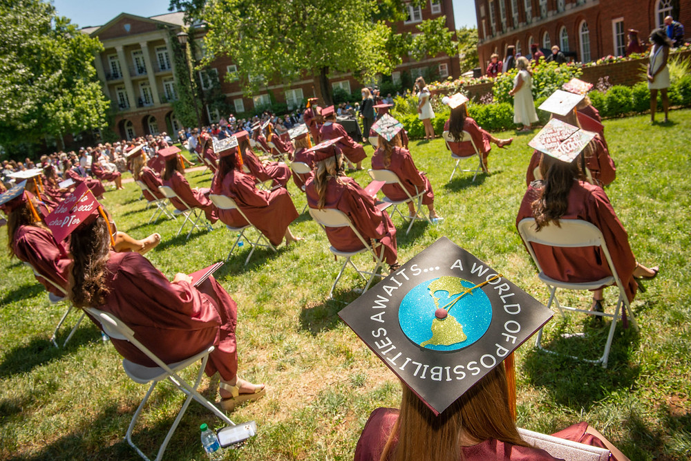 Graduating students sitting behind Johnson Hall in their caps and gowns