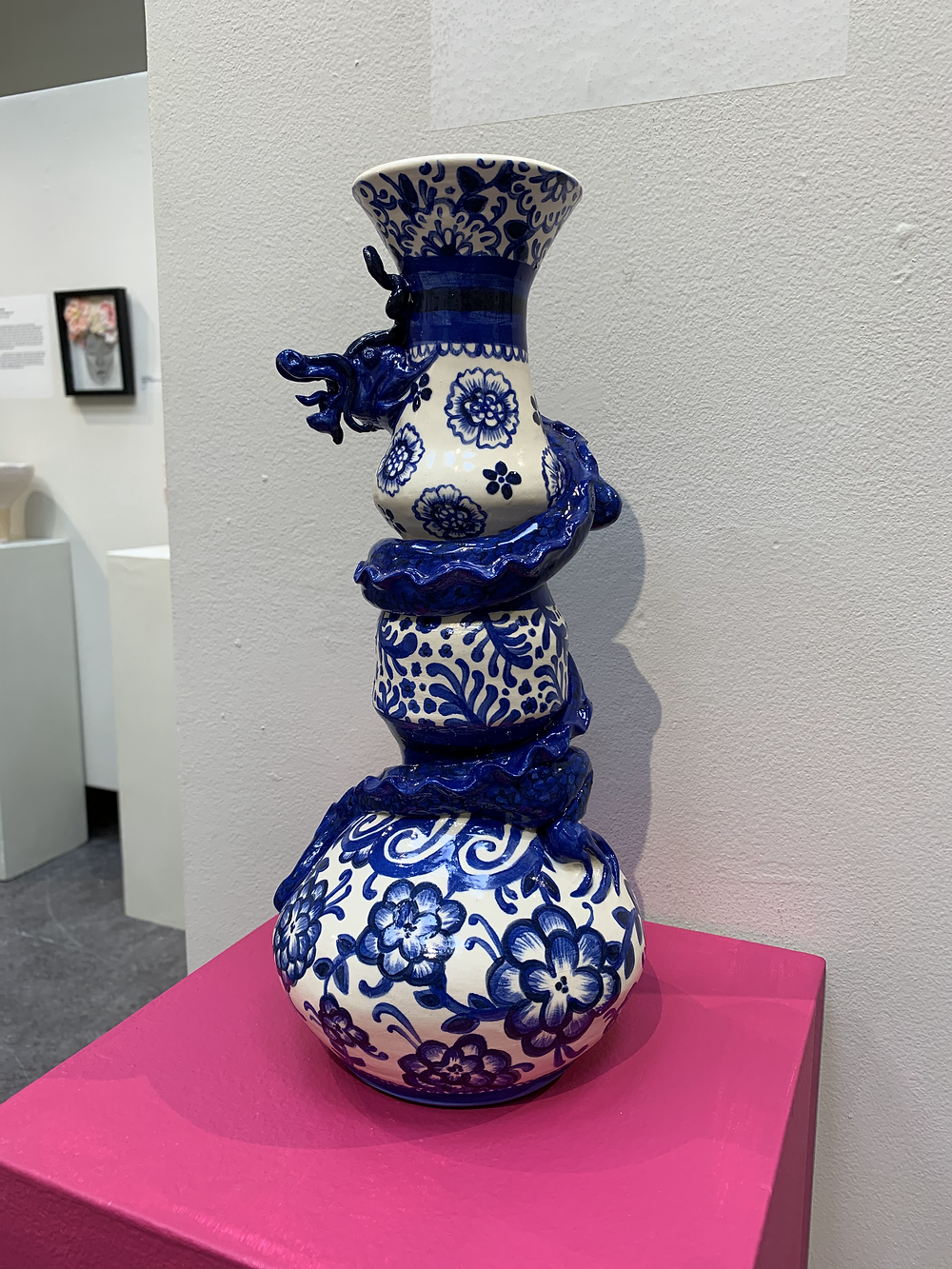 A blue and white ceramic vase with a dragon coiled around it