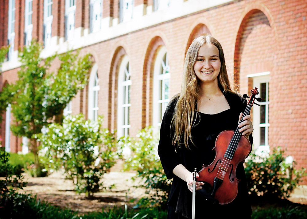 Krista standing by Johnson Hall, holding her violin
