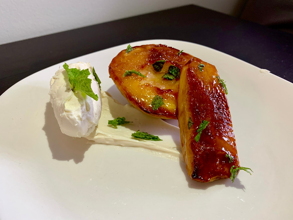 A carmelized peach on a plate with a swoosh of mascarpone and mint leaved