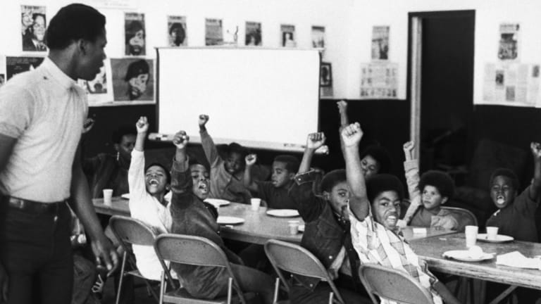 Black students raising their fists as a symbol of Black power