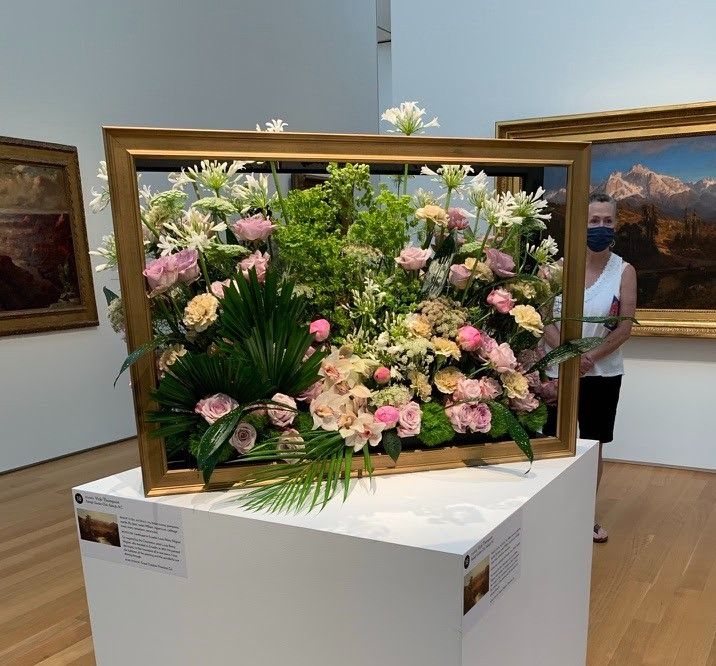 An arrangement with much greenery, including palm fronds, and some pink flowers, inside a picture frame,