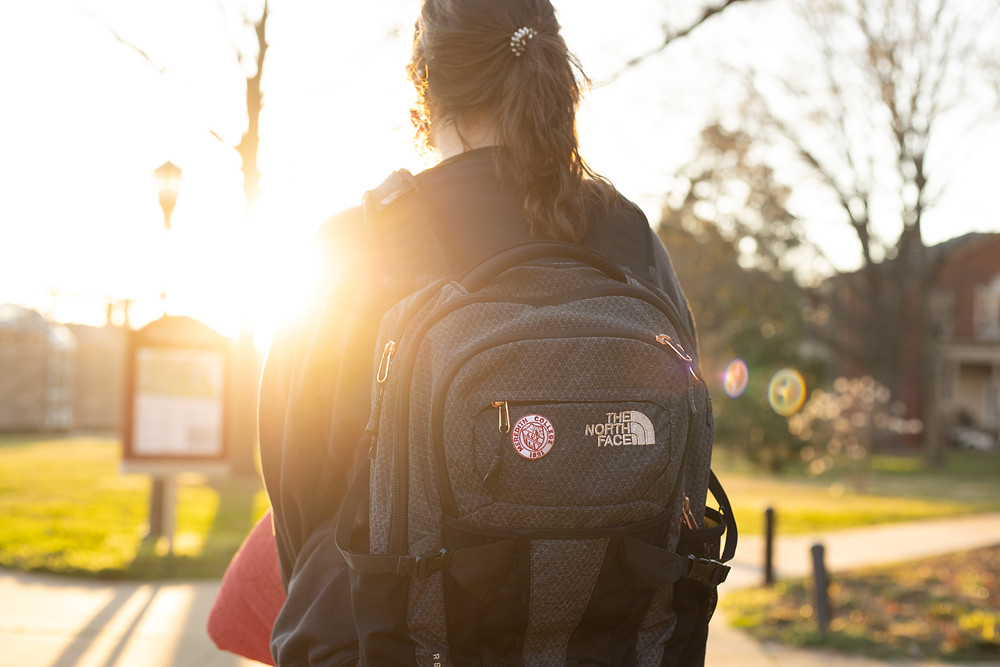 A photo shot from behind a student wearing a backpack on Meredith's campus