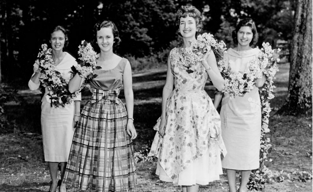A black and white photo of four women holding flower chains