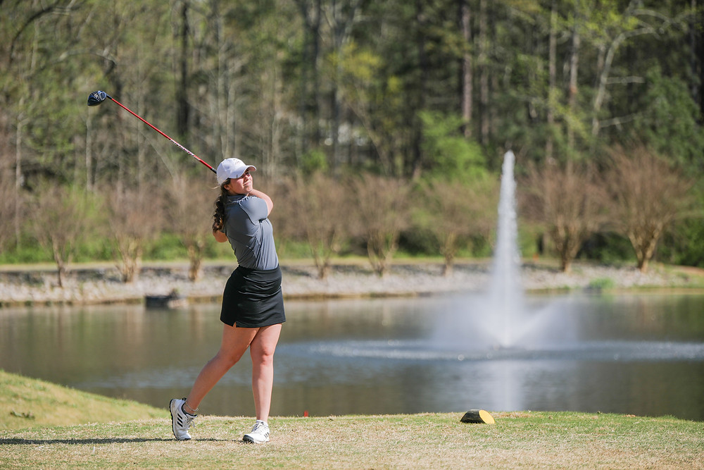 A member of Meredith's golf team hitting the ball in front of a golf course lake