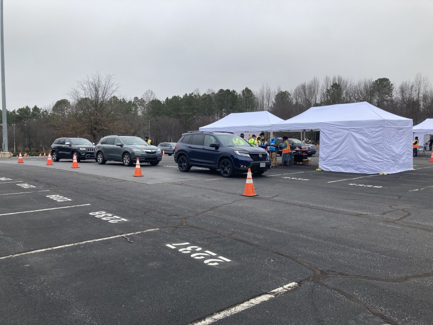 A drive through COVID-19 vaccine station with white tents and 3 cars