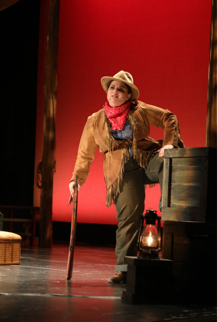 A girl dressed in Old West clothes on a stage with a red background