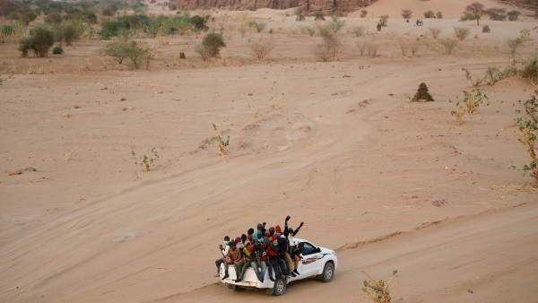 Wide-shot photo of a group of migrants and refugees sit in the back of a white pick-up truck as it drives across the desert.