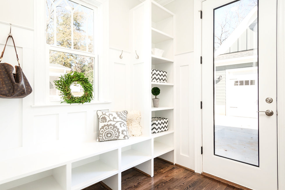 Clean and organized white entryway mudroom with cubbys and bins, decorative pillows, wreath and hanging handbag