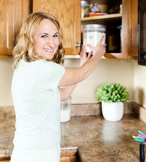 Professional Organizer Amy in the kitchen placing a labeled container in a corner cupboard