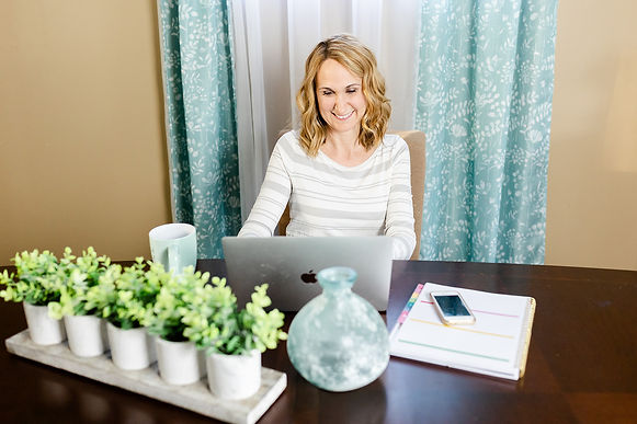 Professional Organizer of Simplified by AT, Amy sitting at a desk looking at her Apple computer with a coffee mug, planner, cell phone, vase and decorative plants on the desk