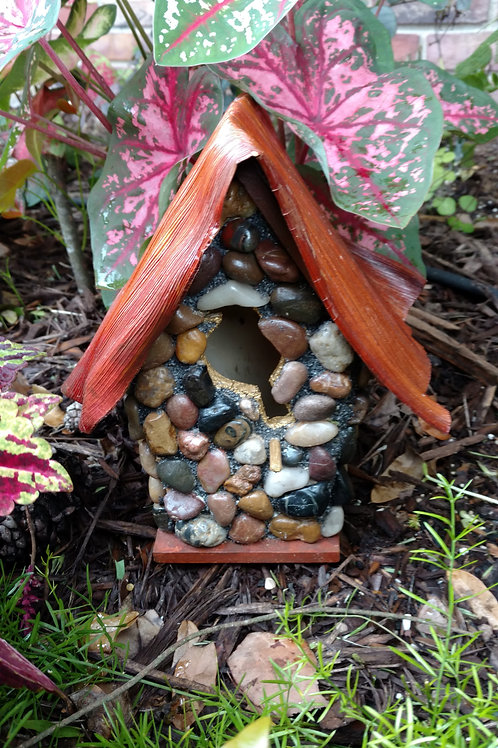 Stone bird house with palm leaf roof