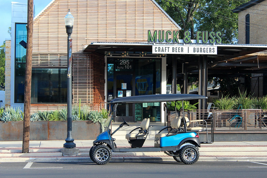 A blue golf cart parked in front of Muck & Fuss, a local craft beer and burger restaurant.
