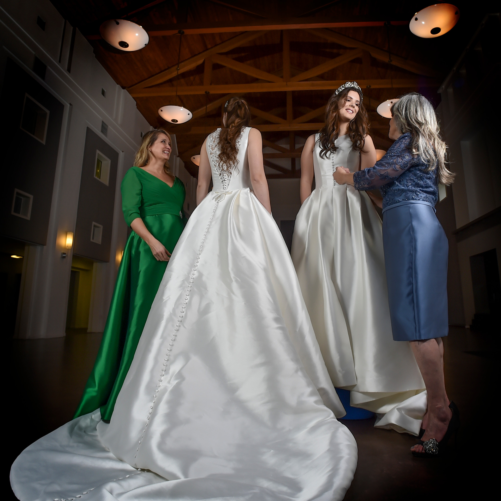 Kathy looks glamorous in the Pronovias Evenings gown of shamrock green 3/4 chiffon sleeve and Makato ballgown skirt with pockets. The surplice wrap creating a sloping v-neck and cinched waist showcases an hourglass look for this Mother of the Bride.   Charlene is wearing a lovely Marine Blue Occasions by Mon CheriMother of the Bride dress of embroidered and beaded net bodice and Makato straight skirt with banded waist. --- Lindsey and Maggie are showcasing Pronovias full skirted, sleeveless silk makato ballgowns with pockets! the covered button detail on the front and back of Maggie's gown is both classic and modern...with the added feature of a front slit to allow for easy movement. Lindsey's gown has a peak a boo back with lace and covered buttons as the decoration focus of this piece. Crowning glory by Symphony in gorgeous tiaras encrusted with crystals in royal crown replicas.