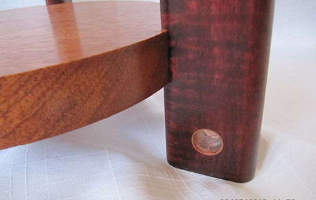 round mahogany table with gently curved coloured tiger maple with copper inserts