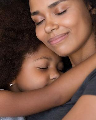 Loving single black mother hugs cute dau