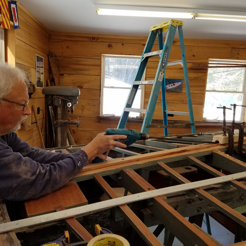 """""""Phil the Drill"""" drilling the new keel for the prop shaft using a pilot drill through a metal jig to ensure the correct angle."""