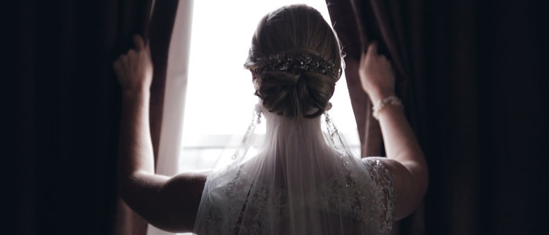 Majilla, the bride opens the curtain during her photo session taken while getting ready at the Cambridge Hotel