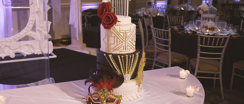 The beautiful custom-made wedding cake has black and white details and two red roses