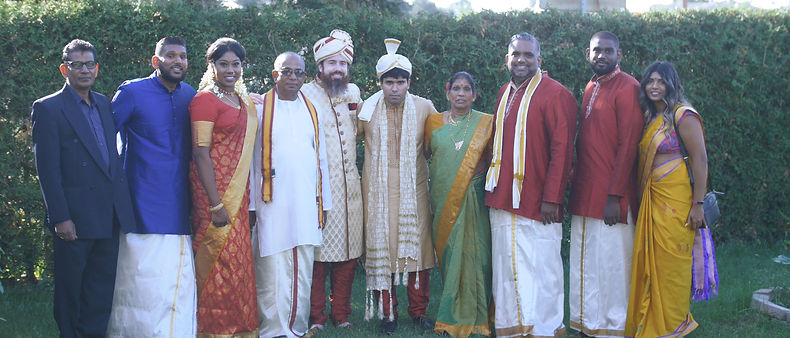 The groom poses for a picture with his family and the bride's relatives.