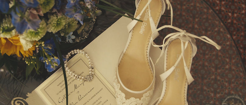 A shot of the bracelet, wedding invitation, shoes and bouquet