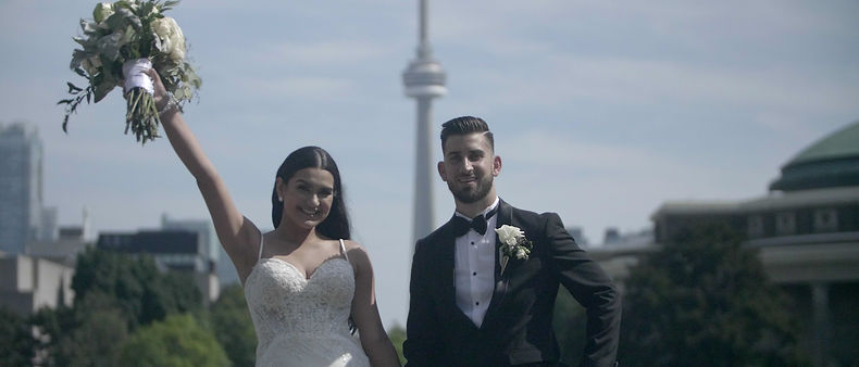 The couple pose for a picture with the CN tower in the background.