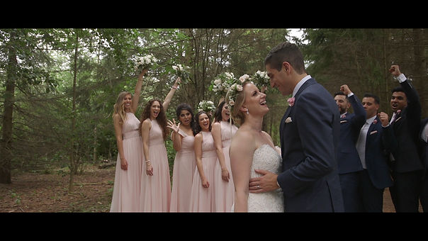 The couple look in love while the bridal party cheer during a Movi shot.