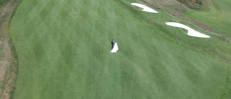 A drone shot of the bride and the groom out on the middle of the golf course