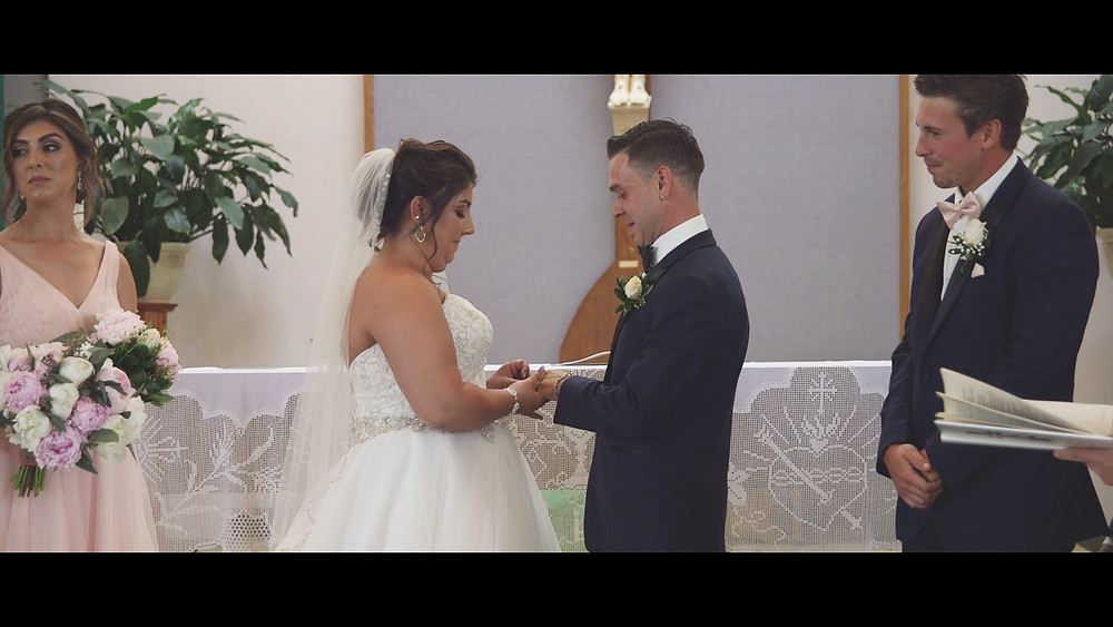 The videographer captures the ring exchanging during the ceremony