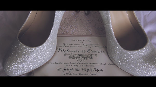 Detail shots: the bride's shoes and the wedding invitation