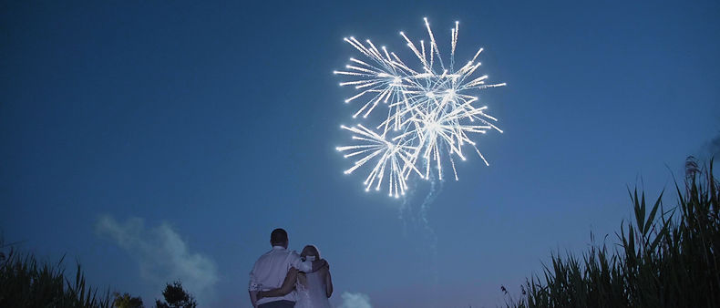 Couple posing for a picture with fireworks.