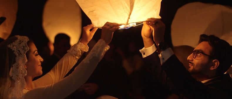 Wedding flying lanterns held by guests and the couple