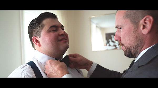 Jarek stands tall while the groomsman fixes his bowtie.