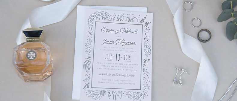 Detail shot from the morning of the wedding. Wedding invitation, wedding rings and the bride's cologne