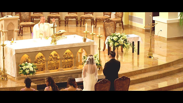 The couple listens to the priest speaking during the mass portion of their wedding ceremony.
