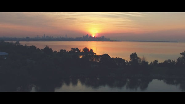 A beautiful image of Toronto's skyline seen from above during sunrise hour.