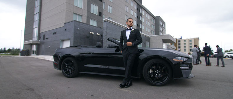 Groom dressed up and his convertible Ford Mustang