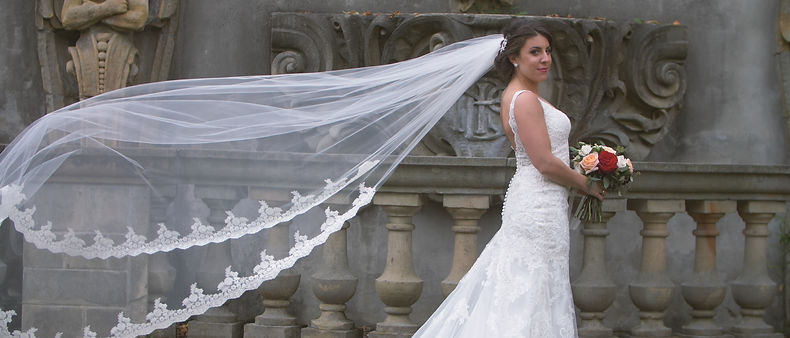 Cassie poses for a photo and shows her beautiful long wedding veil.