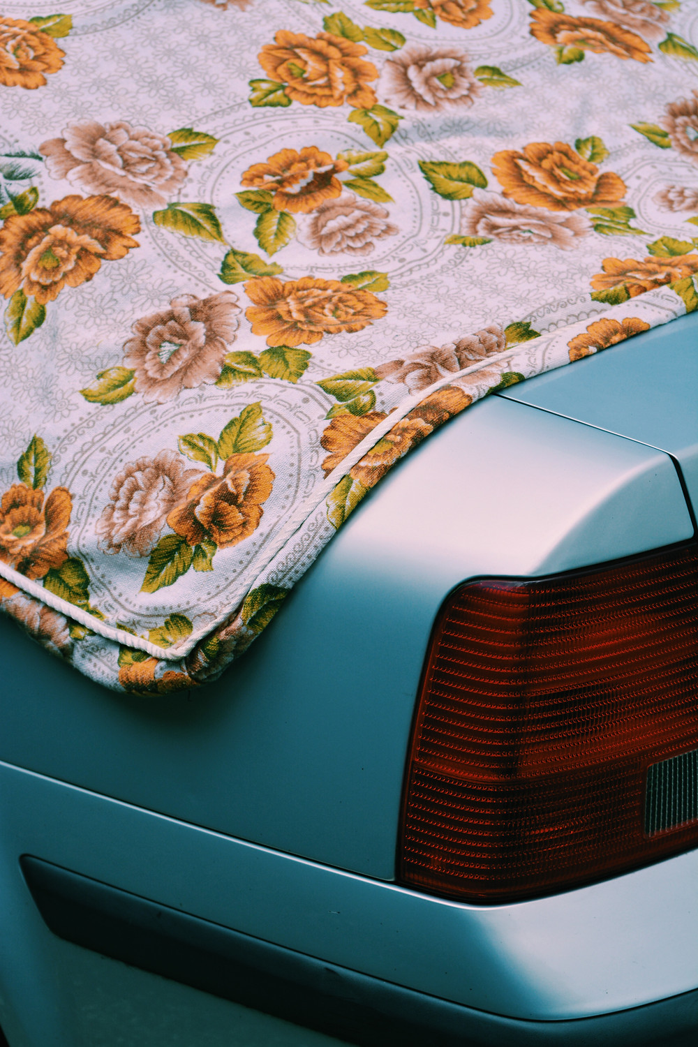 Close up of the left rear light of a light blue car. A flowery quilt is laid on top of it.