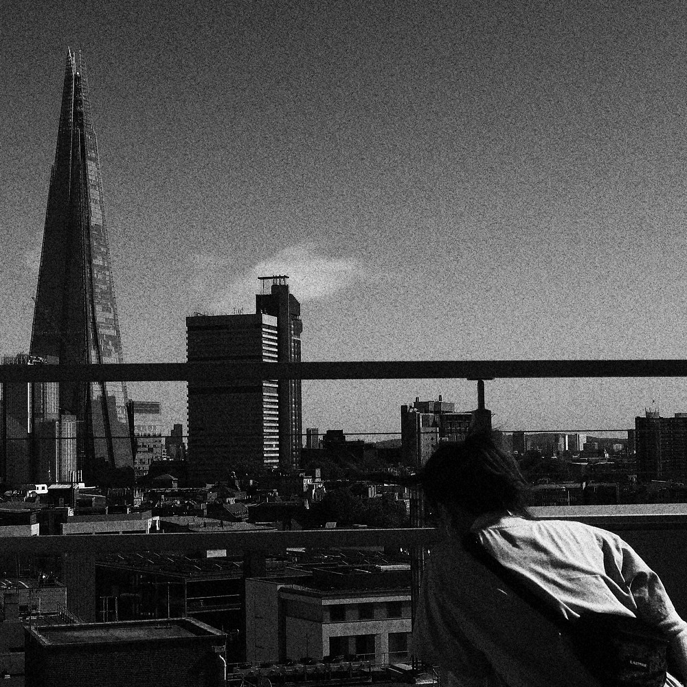 A woman on the right of a rooftop is in the process of ducking, facing The Shard. The picture is a grainy black and white.