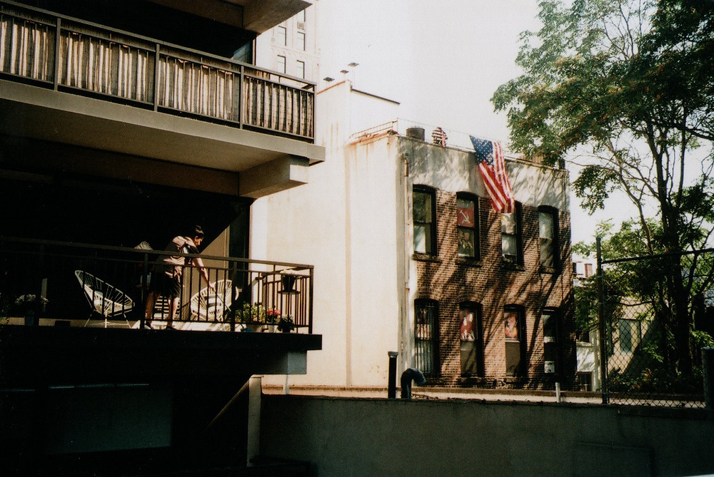 Some buildings and their balconies. In one of the latter, a woman is cleaning. From another building hangs a billowing American flag. There are green trees to its left, althought the photo is dominated by brown and white hues.