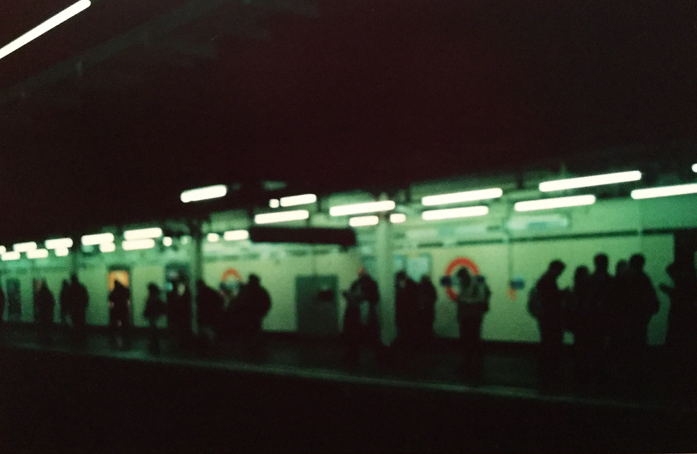 A blury picture of people waiting at a London tube platform. The picture is dominated by green and black hues.