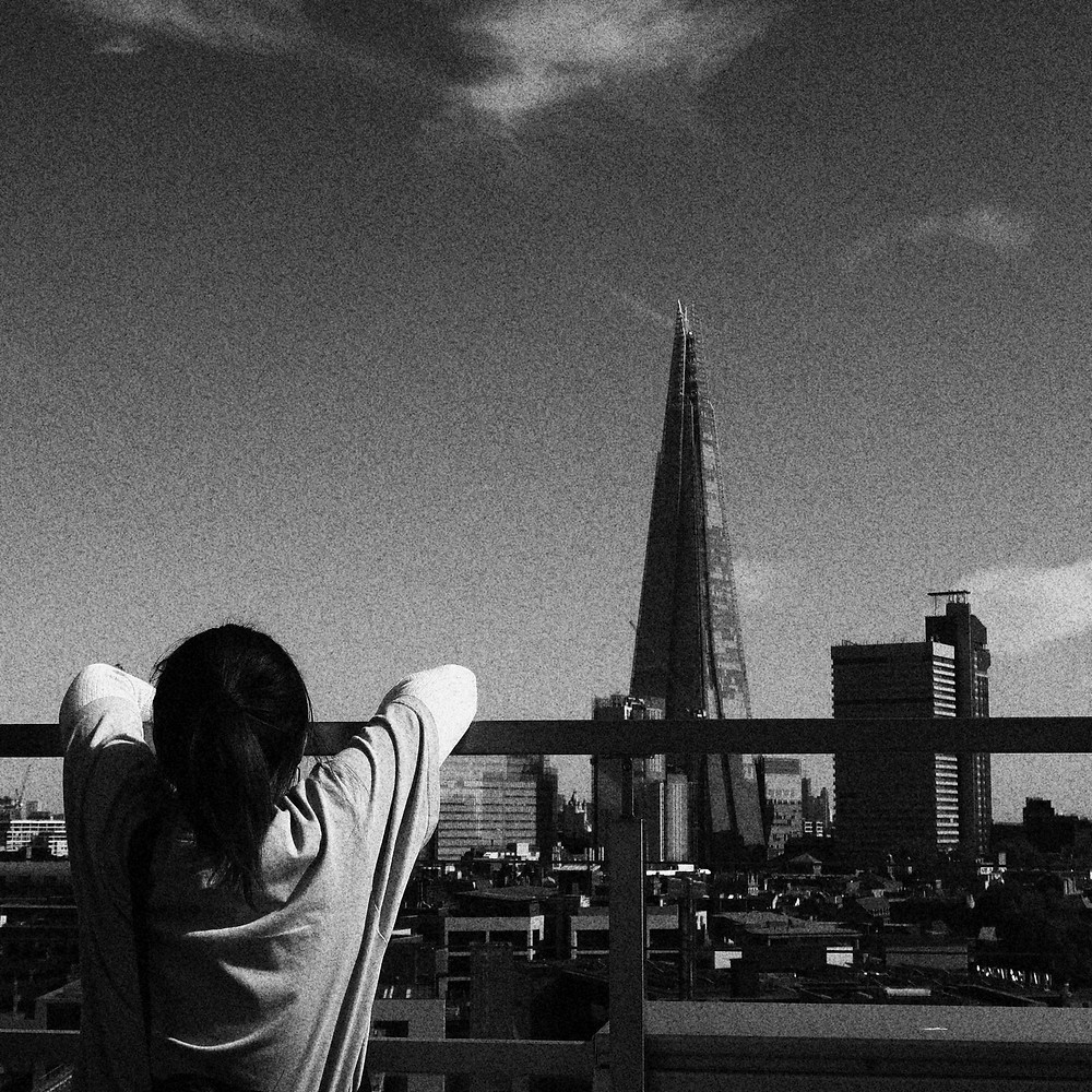 A woman on the left of a rooftop is leaning on the guard rail, looking at The Shard. The picture is a grainy black and white.