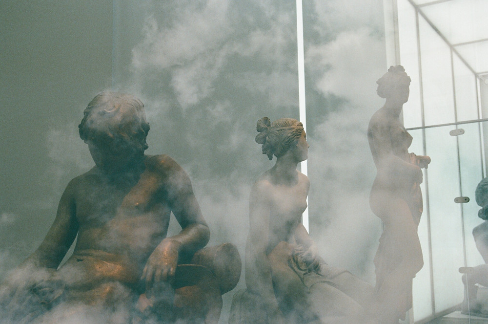 Three greek statues surrounded by smoke.