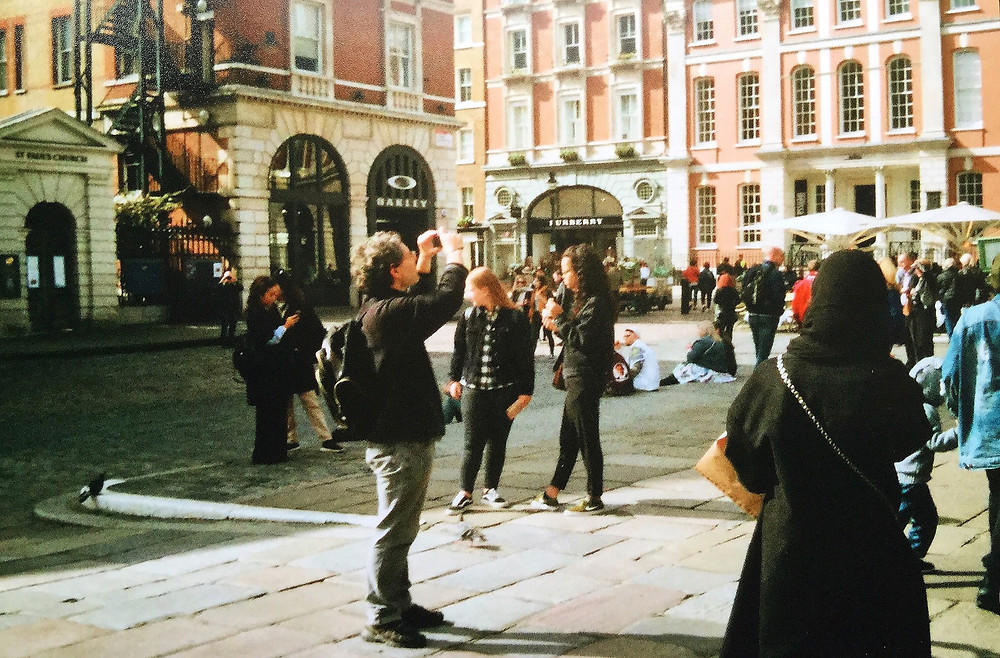 Picture of a man - likely a tourist - taking a photograph with his phone in the middle of a crowded London plaza.